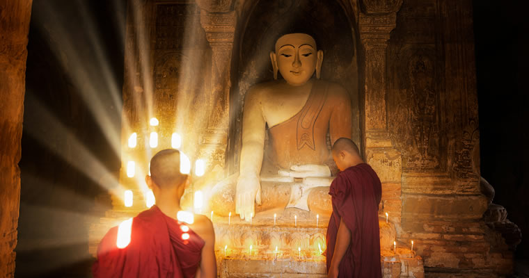Young Monk with Buddha Statue