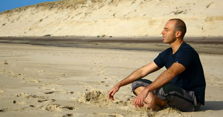 Man meditating on a beach